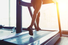 Fitness girl running on treadmill Stock Images