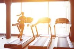 Fitness girl running on treadmill Royalty Free Stock Photography