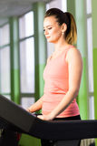 Fitness girl running on treadmill. Woman with muscular legs in gym stock images