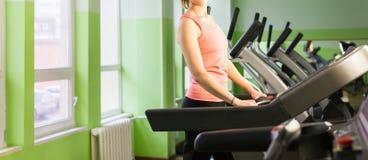 Fitness girl running on treadmill. Royalty Free Stock Photos