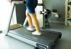 Fitness girl running on treadmill. Woman in gym Royalty Free Stock Photo