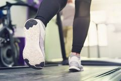 Fitness girl running on treadmill. Woman with muscular legs in modern gym, a girl in white sneakers running on a treadmill in the. Fitness girl running on stock photography
