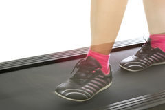 Fitness girl running on treadmill. Woman with muscular legs on w Stock Photography