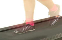 Fitness girl running on treadmill. Woman with muscular legs on w Royalty Free Stock Photo