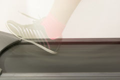 Fitness girl running on treadmill. Woman with muscular legs on w Stock Photo