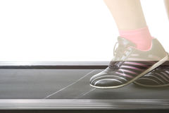Fitness girl running on treadmill. Woman with muscular legs on w Royalty Free Stock Photography
