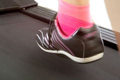 Fitness girl running on treadmill. Woman with muscular legs on w Royalty Free Stock Photos