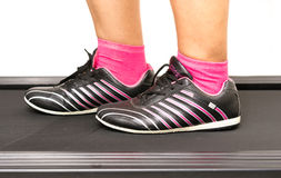Fitness girl running on treadmill. Woman with muscular legs on w Royalty Free Stock Images