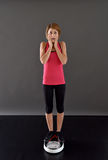 Fitness girl on scale being surprised Royalty Free Stock Photo