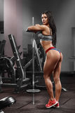 Fitness girl, sexy athletic woman working out with barbell in gym. Sexy beautiful ass in thong Royalty Free Stock Photos