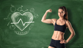 Fitness girl showing her bicep on the background of a chalkboard with drawn beating heart and sport doodles