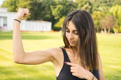 Fitness girl showing her well trained biceps. After working out outdoors Royalty Free Stock Photos