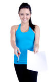Fitness girl sign up. Studio shot of a Fitness girl isolated on white offering pen and paper to sign up (gym contract Royalty Free Stock Photos