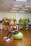 Fitness, girl sitting on the ball. Fitness, girl sitting on ball in fitness and smiles Royalty Free Stock Image