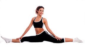 Fitness girl sitting and stretching her legs Royalty Free Stock Image