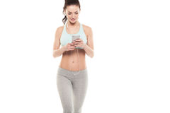 Fitness girl with a smartphone on a white background, enjoys sports training, gym workout Royalty Free Stock Photos