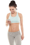 Fitness girl with a smartphone on a white background, enjoys sports training, gym workout Royalty Free Stock Photography