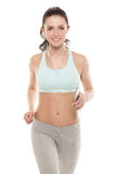 Fitness girl with a smartphone on a white background, enjoys sports training, gym workout Stock Image