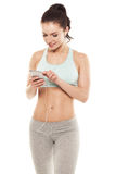 Fitness girl with a smartphone on a white background royalty free stock photos