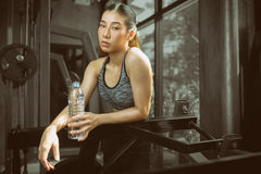Fitness girl in sport club with exercise equipments. Stock Photos