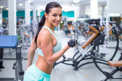 Fitness girl in sport club. Photo of beautiful young sporty woman. Fitness girl training with dumbbells in sport club with exercise equipments. Woman smiling and Royalty Free Stock Photo