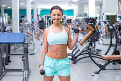 Fitness girl in sport club. Photo of beautiful young sporty woman. Fitness girl training with dumbbells in sport club with exercise equipments. Woman smiling and Royalty Free Stock Photos