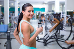 Fitness girl in sport club. Photo of beautiful young sporty woman. Fitness girl training in sport club with exercise equipments. Woman holding bottle of water Stock Photo