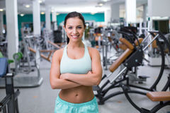Fitness girl in sport club. Photo of beautiful young sporty woman. Fitness girl training in sport club with exercise equipments. Woman smiling and looking at Royalty Free Stock Photo