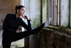Fitness girl stretching in abandoned building before workout Stock Photo