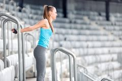 Fitness girl stretching and doing gymnastics exercises on stadium stairs. Athlete girl and people working out concept royalty free stock image