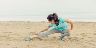 Fitness girl stretching her legs Stock Photos