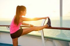 Fitness girl stretching leg on cruise vacation. Young woman adult doing stretches after running workout at sunset on balcony of a cruise ship during summer Royalty Free Stock Image