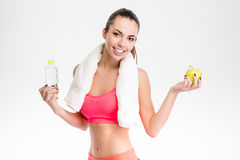 Fitness girl with towel holding bottle of water and apple Stock Image