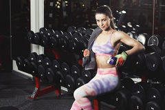 Fitness girl with towel and shaker relaxing in the gym royalty free stock images