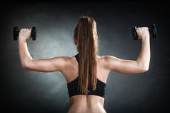 Fitness girl training shoulder muscles back view. Fitness girl fit woman lifting dumbbells weights doing exercise with dumb bells training shoulder muscles back royalty free stock photos