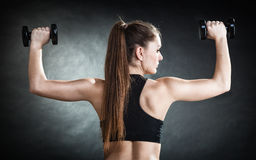 Fitness girl training shoulder muscles lifting dumbbells back view. Fitness girl fit woman lifting dumbbells weights doing exercise with dumb bells training stock photography