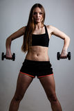 Fitness girl training shoulder muscles lifting dumbbells. Fitness girl fit woman lifting dumbbells weights doing exercise with dumb bells training shoulder stock image