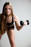Fitness girl training shoulder muscles lifting dumbbells. Fitness girl fit woman lifting dumbbells weights doing exercise with dumb bells training shoulder stock photo
