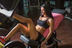 Woman on leg press. Attractive young woman exercising in the gym on a bench press Royalty Free Stock Photography