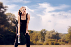 Fitness Girl with Water Bottle Hydrating after Outdoor Workout. Fit woman taking a break from exercising Royalty Free Stock Photography