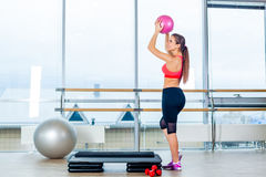 Fitness girl, wearing in sneakers, red top and black  breeches, posing on step board with ball, the sport equipment Royalty Free Stock Photography