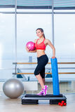 Fitness girl, wearing in sneakers, red top and black  breeches, posing on step board with ball, the sport equipment Stock Images