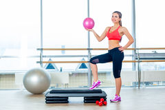 Fitness girl, wearing in sneakers, red top and black  breeches, posing on step board with ball, the sport equipment Stock Photo