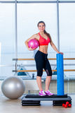 Fitness girl, wearing in sneakers, red top and black  breeches, posing on step board with ball, the sport equipment Stock Photos