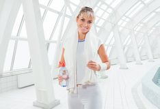 A fitness girl wearing white sports clothes with white towel and Stock Photo