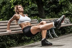 Fitness girl is working out in the park Stock Photos