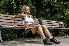 Fitness girl is working out in the park Stock Images