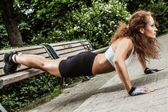 Fitness girl is working out in the park Stock Photography
