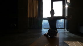 Fitness girl yoga silhouette in the room stock video