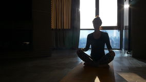 Fitness girl yoga silhouette in the room stock video footage